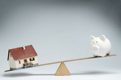 Home loans market. Model house and piggy bank balancing on a seesaw Stock Photos