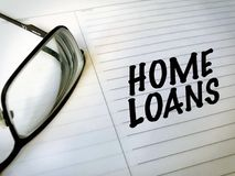 Home loans and mortgages. Home loans with notebook and glasses Royalty Free Stock Images
