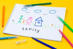 Home, love, family, still life concept. felt-tip pen lying on a paper with children`s drawing family. Selective focus, copy space