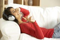 home lyssnande musik till kvinnabarn Arkivfoton