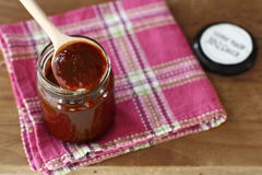 Home made barbecue sauce. In a jar with a wooden spoon Stock Photography