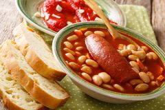 Home-made bean soup with sausage is served with bread and bell p. Epper close-up on the table. horizontal royalty free stock photo