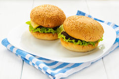 Home made beef burgers on plate and napkin. White wooden background Stock Image