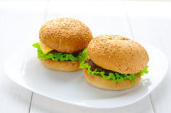Home made beef burgers on plate. White wooden background Royalty Free Stock Images