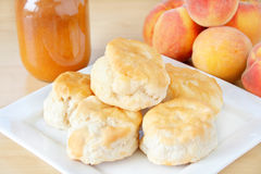 Home made Biscuits. Fresh home made biscuits stacked on a white plate with home made peach preserves in the background along with fresh peaches royalty free stock photo