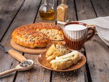 Home-made bread in a cut and a slice of sliced bread smeared with butter and a mug of milk on a plank rustic table, next to wooden stock photography