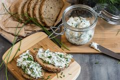 Home made bread on a wooden cutting board with curd cheese and ricotta and herbs. Decorated with green herbs royalty free stock photo