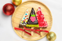 Home made brownies winter tree shape with red bow and ribbon on. Wooden plate; christmas glitter ball on white background stock image