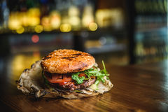 Home made burger. The Burger on the burnt paper on wooden background Royalty Free Stock Images