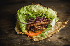 Home made burger. The Burger on the burnt paper on wooden background Royalty Free Stock Image