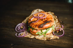 Home made burger. The Burger on the burnt paper on wooden background Stock Image
