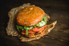 Home made burger. The Burger on the burnt paper on wooden background Royalty Free Stock Photos