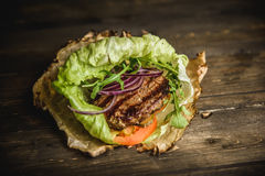 Home made burger. The Burger on the burnt paper on wooden background Stock Images