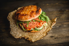 Home made burger. The Burger on the burnt paper on wooden background Stock Photo