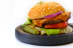 Home made burger, close up view. Close up view on a classical home made burger lying on wooden plate. You may see quite large wide and fat burger with lots of royalty free stock images