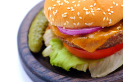Home made burger, close up view. Close up view on a popular fast food: a classical burger lying on wooden plate. You may see quite large wide and fat burger with Stock Image