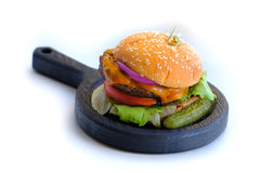 Home made burger, fast food. Close up view on a classical home made burger lying on a stylish thick wooden pan. You may see quite large wide and fat burger with Royalty Free Stock Photos
