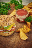Home made burger. Fresh tasty burger with potato wedges and sauce on wooden table Stock Images