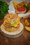 Home made burger. Fresh tasty burger with potato wedges and sauce on wooden table Royalty Free Stock Image