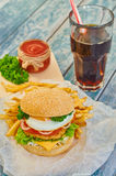 Home made burger on wooden background. Fresh tasty burger with french fries and cola on wooden table Stock Photos
