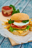 Home made burger on wooden background. Fresh tasty burger with french fries and sauce on wooden table Royalty Free Stock Photography