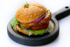 Home made burger, wooden pan. Close up view on a classical home made burger lying on a stylish thick wooden pan. You may see quite large wide and fat burger with royalty free stock images