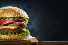 Home made burger on wooden plank on a dark background. Close-up of delicious fresh home made burger with lettuce, cheese, onion and tomato on a rustic wooden Royalty Free Stock Photos