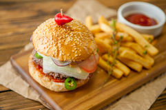 Home made burgers on wooden background Royalty Free Stock Photo