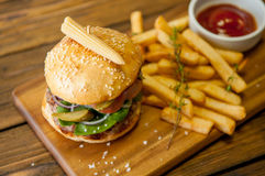Home made burgers on wooden background Stock Images