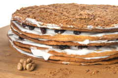 Home made cake decorated with nuts, raisins and white cream Stock Photography