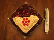 Home made cake. Home made strawberry cake with berry-sauce on top. Frosting ribbon and maraschino cherries used for garnishing. Cake is placed on a square glass royalty free stock images