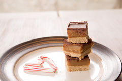 Home Made Caramel Treats for Christmas. Home made caramel bar treats with candy cane Stock Photo