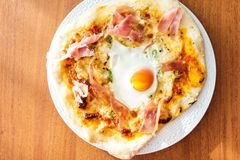 Home made cheese, prosciutto and egg pizza Royalty Free Stock Photography