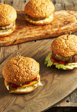 Home made cheeseburgers on wooden table Stock Images