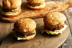 Home made cheeseburgers on wooden table Royalty Free Stock Images