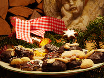 Home made Christmas cookies. Close up of home made Christmas cookies and gingerbread, lebkuchen, decorated with brushwood, stone angel and woodpile in the Stock Image