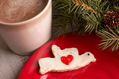 Home made Christmas dove heart cookie with hot chocolate. And evergreen boughs Stock Photo