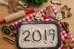 Home made Christmas gingerbread cookies with 2019 written on flour. With a festive background on a table royalty free stock photography