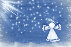 Home made Christmas paper angel on blue, snowy wooden background.Craft Stock Image