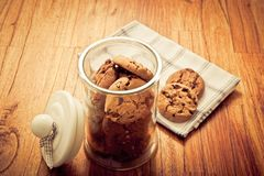 Home made cookies biscuits with cacao chips in glass jar in rustic style. On wooden background like sweet, healthy cereal dessert, food concept, sweets and home royalty free stock image