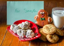 Home made cookies for Santa. Snicker-doodles and Mexican wedding cookies, a cold glass of milk and a note for Santa too Stock Image