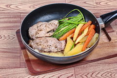 Home made ,Cooking pork steak with mixed vegetables in pan before served. Royalty Free Stock Photo