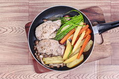 Home made ,Cooking pork steak with mixed vegetables in pan before served. Royalty Free Stock Photography