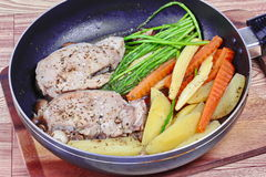 Home made ,Cooking pork steak with mixed vegetables in pan before served. Stock Photos