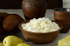 Home-made cottage cheese in earthenware, clay cup of milk, pears Royalty Free Stock Photography