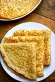 Home made crepes. Thin folded puncakes laid on a white plate Royalty Free Stock Images
