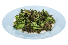 Home made Crispy Baked Kale Crisps or Chips Served on Blue Plate Stock Photography