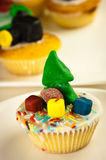 Home-Made cupcake with Christmas Tree. Home-made cupcake with a Christmas Tree decoration. Out of focus cupcakes in the background stock photo