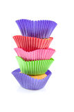 Home made cupcakes. Stacked home made cupcakes in colorful cups, isolated on white background Stock Photography