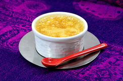 Home-made custard with a red ceramic spoon Stock Images